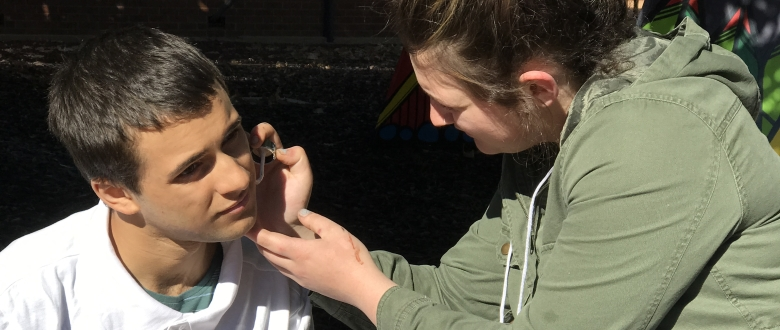 "Dayna Behsman applying make-up to actor Jordan Davis on the set of ""Zit"""